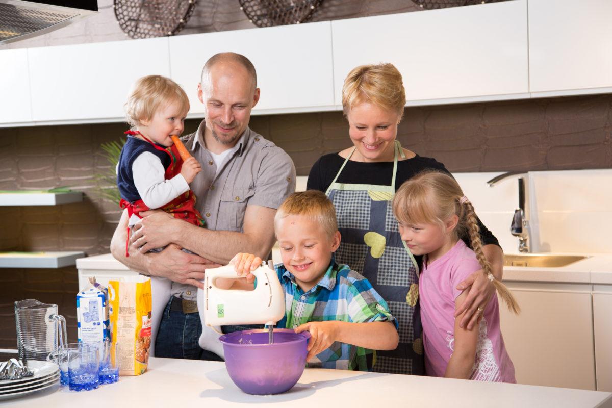 Onnellinen perhe keittiössä